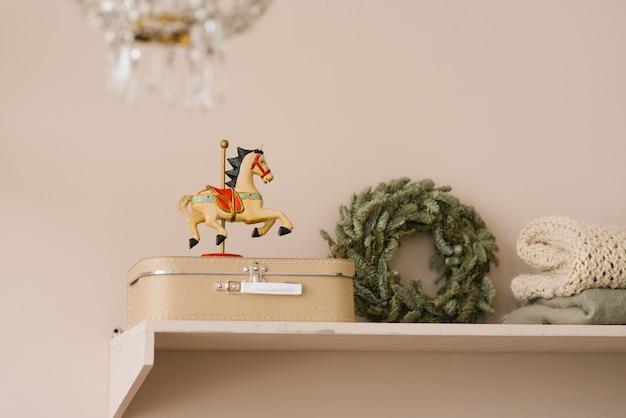 Деревянная игрушка лошадь на бежевом чемодане на полке и рождественский венок