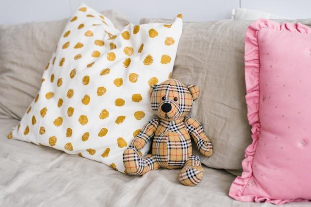 ベッドの枕の中で柔らかいおもちゃ格子縞のクマ