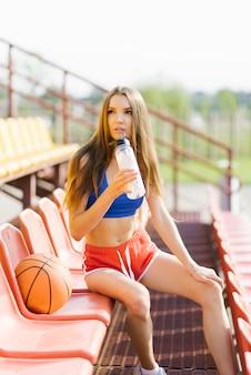 Стройная спортивная девушка в коротких выстрелах и топе пьет воду из стеклянной бутылки, она сидит на месте на стадионе, рядом с ней лежит баскетбольный мяч