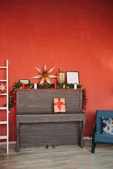 赤い壁の背景にピアノとクリスマスの装飾