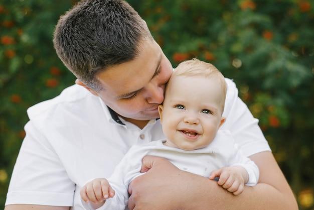 Отец держит своего маленького сына на руках и целует его. ребенок улыбается и счастлив. день отца