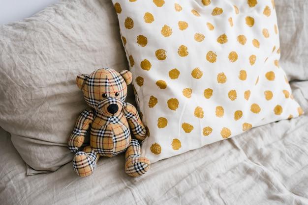 Мягкая игрушка мишка в клетку рядом с подушками на кровати