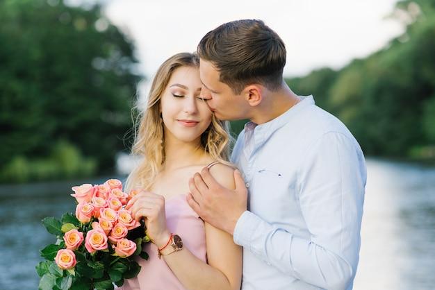 Нежный и трепетный поцелуй в щеку молодого парня и красивой блондинки на берегу озера. первое свидание и любовь