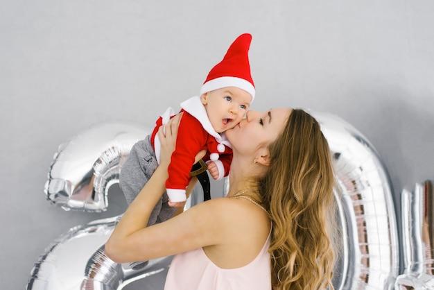 若い母親の手の中の小さなサンタのスーツの赤ちゃん