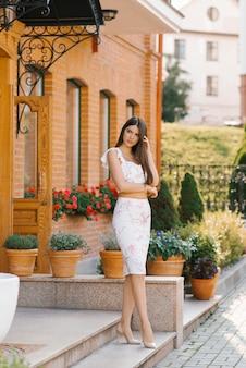 Красивая женщина с длинными волосами и длинными ногами стоит возле дома