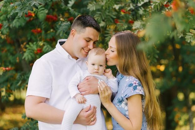 Счастливая и дружная семья целует своего маленького ребенка