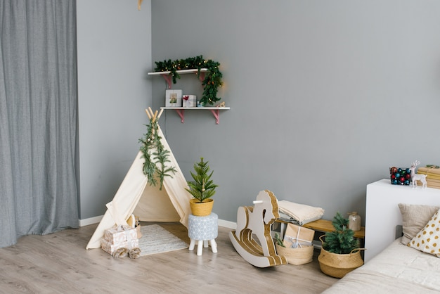 クリスマスと新年のために飾られた子供部屋のインテリア。ウィグワム、ロッキングホース、クリスマスツリー。