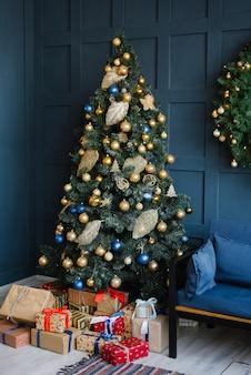 金色と青の風船とその下のプレゼントが付いたクリスマスツリーは、青い壁のあるリビングルームに立っています。