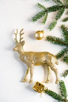 黄金の鹿、クリスマスのおもちゃ、白い背景にスプルースの枝でクリスマスや新年のカードクローズアップ。