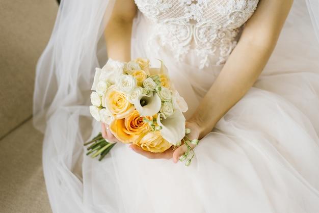 花嫁の手の中の白とオレンジのウェディングブーケ