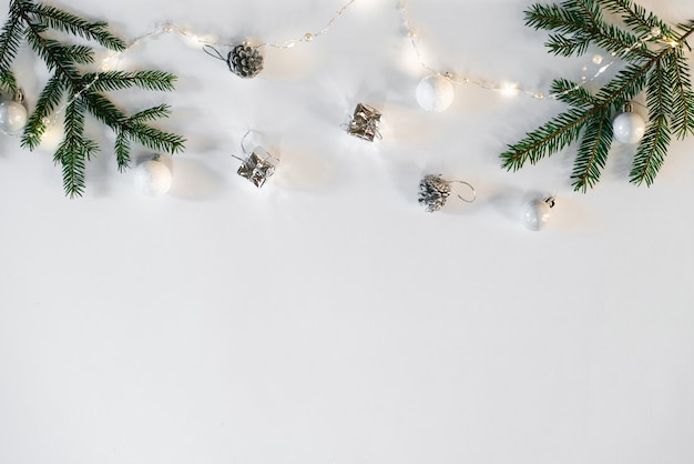 クリスマスと新年の組成。クリスマスのおもちゃ、ライト、ガーランド、スプルースの枝。フラットレイヤー、トップビュー、コピースペース