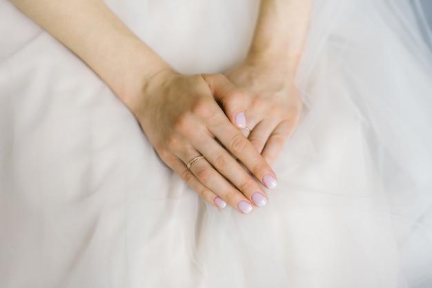 花嫁の手は折り畳まれ、ウェディングドレスに横たわっています