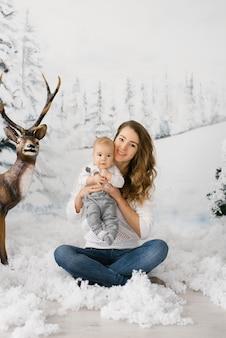 笑顔のママは彼女の腕で彼女のかわいい赤ちゃんを保持しています。