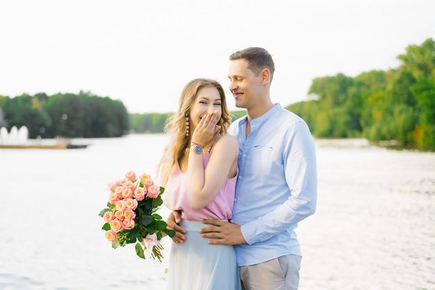 最初のデートで恋に幸せな若いカップル。女性は笑って、バラの花束を持っています。バレンタイン・デー
