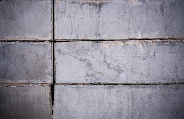 灰色のコンクリートブロックの背景の壁のクローズアップ部分