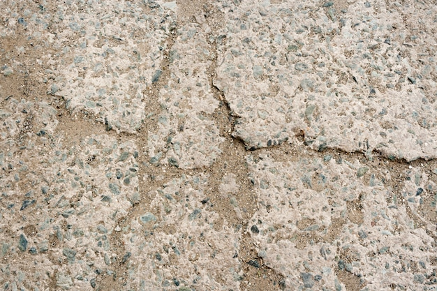 石の背景。小さな小石と砂が入ったコンクリートで作られた舗装の一部で、亀裂に打ち込まれました。
