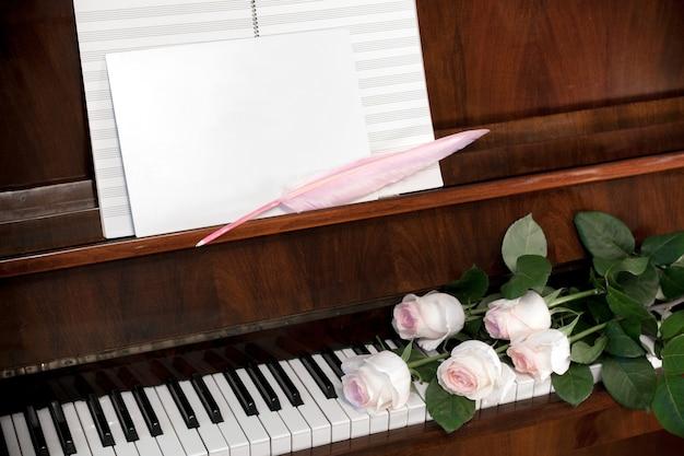 Композиция из бледно-розовых роз, музыкальная бумага и белый чистый лист с розовым пером на коричневом фортепиано.
