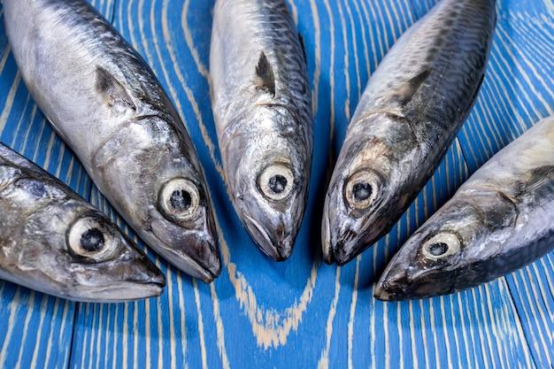 Крупным планом рыбы лежат близко друг к другу на синем фоне деревянных