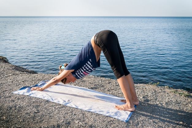 若い女の子は、夏の朝に石の多い海岸でヨガ犬のポーズで立っています。