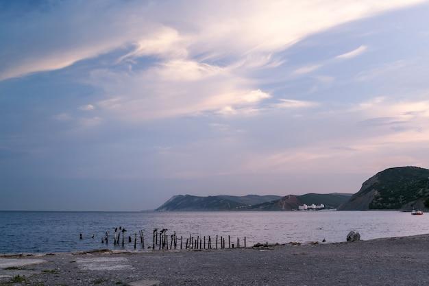 美しい白い雲、山の多い海岸線、石の多い海岸のある海の朝。