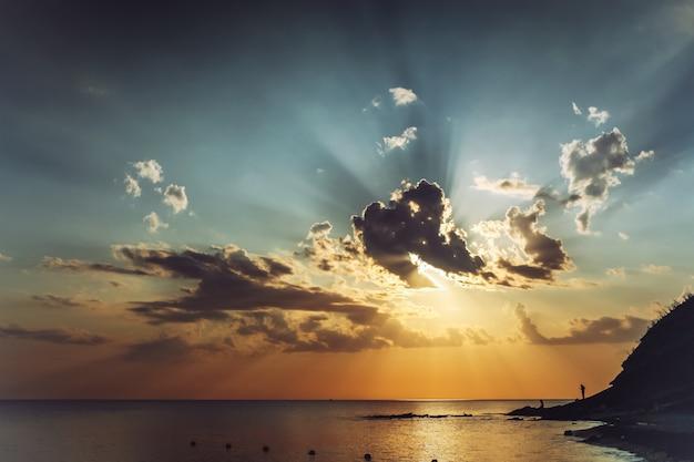 美しい雲と空の太陽光線と夕方の日没前の海景。