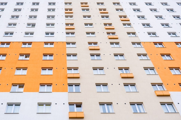 Фасад конца-вверх серо-оранжевого здания с окнами.