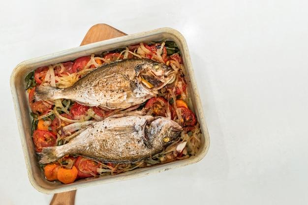 金属製のベーキングトレイの野菜クッションで調理された魚