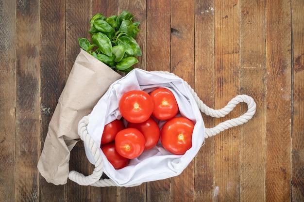 赤いトマトと木製テーブルの上の生態学的な包装の緑のバジル。
