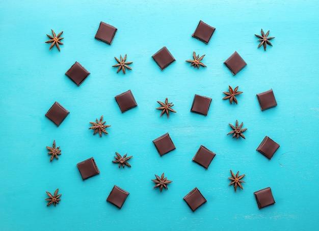 チョコレートスライスとターコイズブルーの背景にアニスの星のパターン