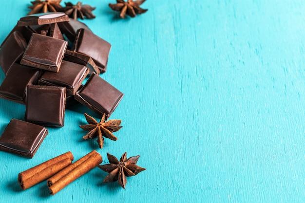 Кусочки шоколада с палочками корицы и аниса на бирюзовом фоне