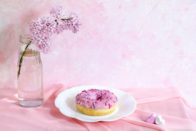 Свежий белый глазированный пончик на фигурную тарелку на белом фоне