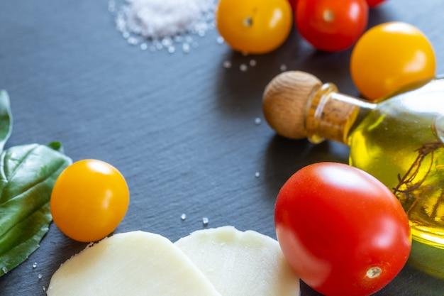 赤と黄色のトマト、モッツァレラチーズ、オリーブオイル、緑のバジル
