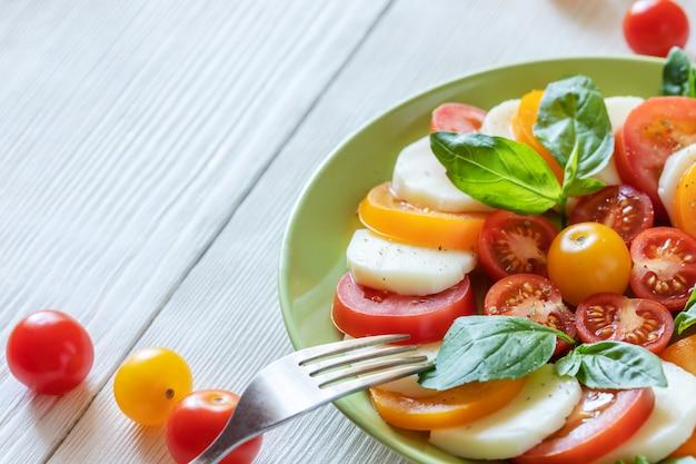 伝統的なイタリアのカプレーゼサラダとクローズアップグリーンプレート