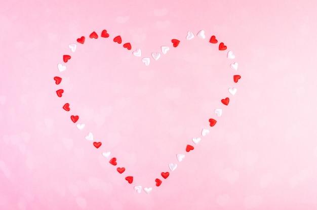 День святого валентина праздничный фон или открытку. маленькие текстильные белые и красные сердечки выложены в форме сердца.