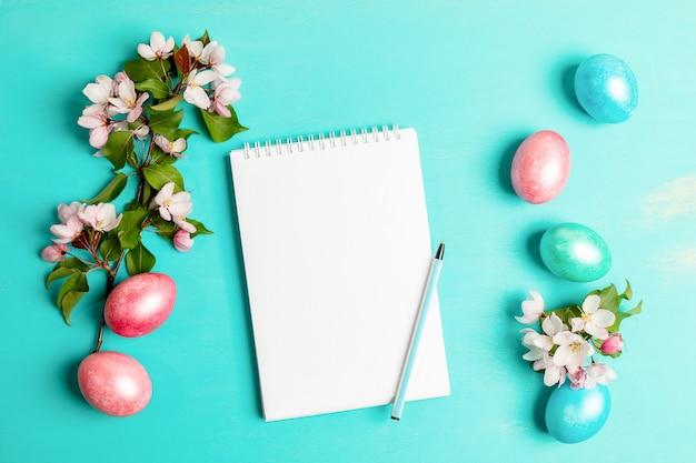 ピンクのリンゴの木の小枝、着色された卵、ペンで白い空白のメモ帳でお祝いイースターレイアウト