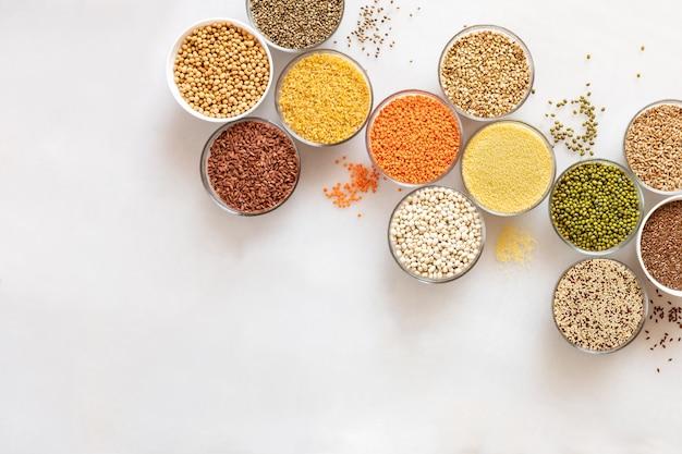 穀物、豆、種子の白い背景の上のコピースペースと斜めのフラットガラスボウル。