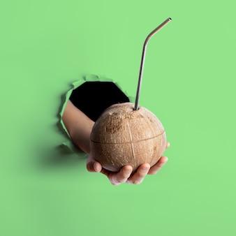 Женская рука протягивая один свежий кокос с металлической соломой, вставленной в нее через рваное отверстие в цветной мятной бумаге нео.