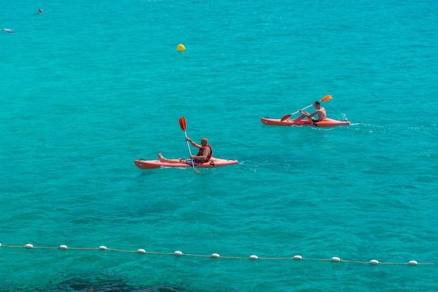 観光客は、人気の地中海湾でカタマランとカヤックで泳ぎます。