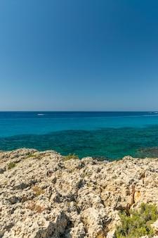 観光客は、地中海の人気の湾でカタマランやカヤックで泳ぎます。