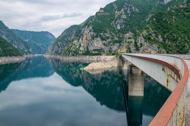 Большой мост пересекает живописное горное озеро