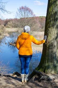女性は冬の服で自然を楽しんでいます