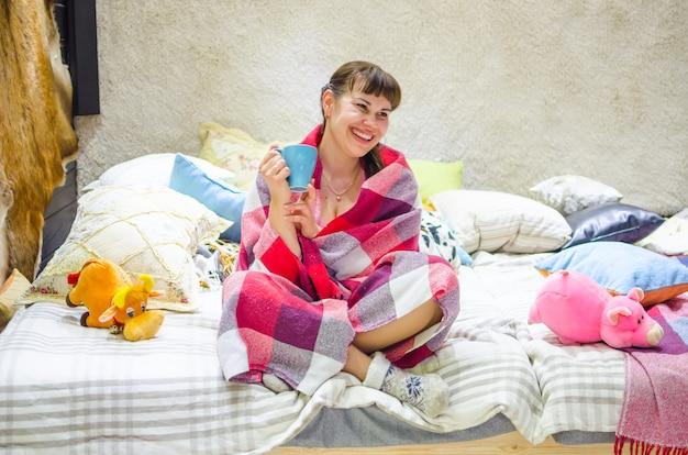 Красивая девушка, греясь под одеялом с чашкой горячего чая.