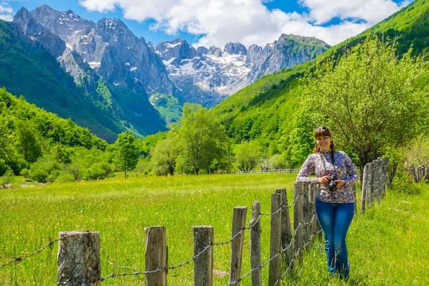 雪をかぶった山を背景にポーズをとる女の子の写真家。