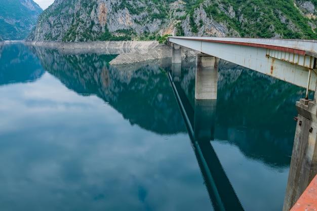 大きな橋は絵のように美しい山の湖にかかっています。