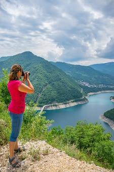 女の子の写真家は、山の頂上から湖の写真を撮ります。