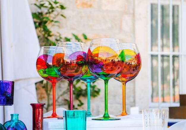 売り手は町の市場でさまざまな色のガラス製品を販売しています。