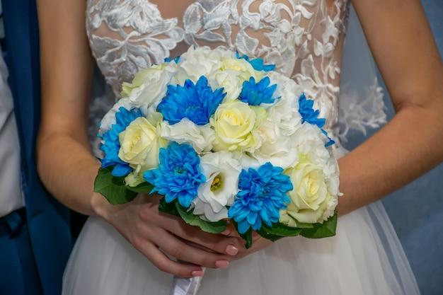 結婚式の最中に、素晴らしい花嫁が結婚式のブーケを手に持っています。