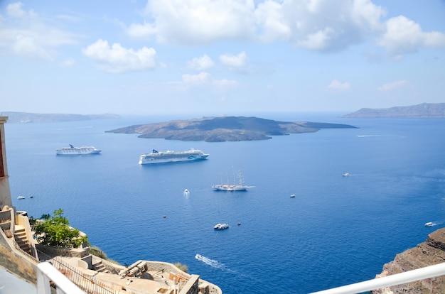 サントリーニ島の美しい島の近くの海を航行する船。