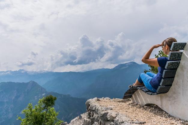 女の子は珍しいベンチに座って山の頂上に横たわっています。