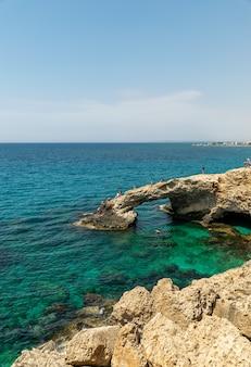Туристы прыгают с высоты в лазурные воды средиземного моря.
